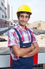 Lächelnder Bauarbeiter mit verschränkten Armen auf Baustelle