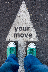 Green shoes standing on your move sign