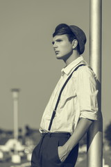 Portrait of a thoughtful young guy with hat and suspenders