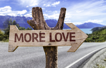 More Love wooden sign with a landscape background