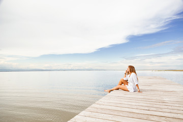 smiling Young woman talking on the phone on a pier