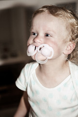 Toddler with two pacifier in her mouth