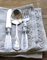 vintage silver cutlery with linen napkin on wooden background