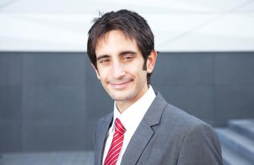 Geschäftsmann mit schwarzen Haaren lächelt zur Kamera