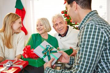Familie überreicht Geschenke zu Weihnachten