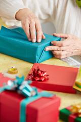 Alte Hände packen Geschenk ein