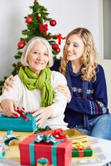Seniorin und Tochter verpacken Geschenk an Weihnachten