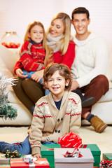Lachender Junge vor Geschenken zu Weihnachten