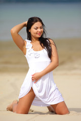 girl on the sand in a white dress