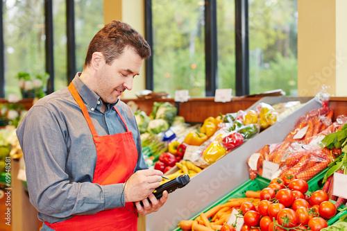 Marktleiter in Supermarkt mit Datenerfassungsgerät - 69948581