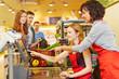 Leinwanddruck Bild - Verkäufer hilft neuer Kassiererin an Kasse