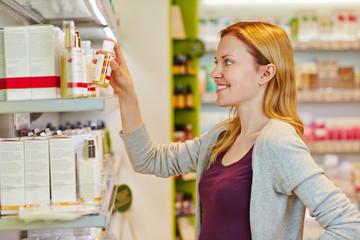 Junge Frau kauft Kosmetik im Supermarkt