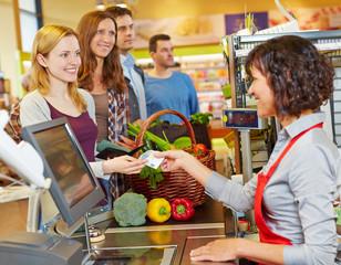 Frau bezahlt mit Geldschein im Supermarkt