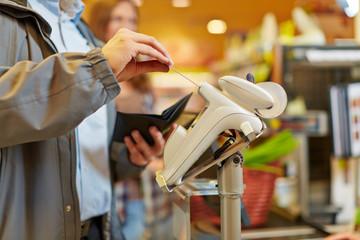 Mann zahlt mit Kreditkarte im Supermarkt