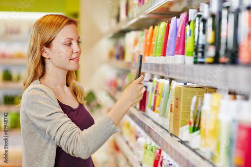 Frau beim Preisvergleich mit Smartphone in Drogerie - 69948742