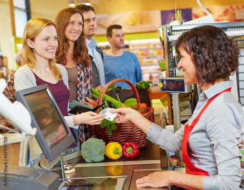 Leinwanddruck Bild Frau bezahlt mit Geldschein im Supermarkt