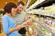 canvas print picture - Verkäufer hilft Frau mit Einkaufsliste im Supermarkt