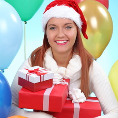 christmas.smiling woman in santa helper hat with gift boxes