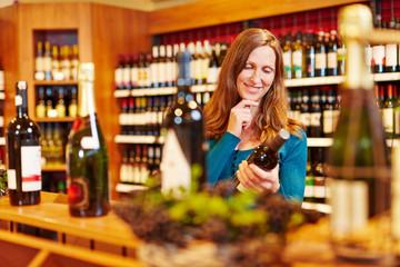 Frau mit Flasche Rotwein im Weinladen