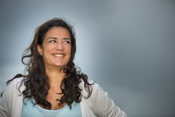 Young woman smiling with dark cloudscape background (copy space)