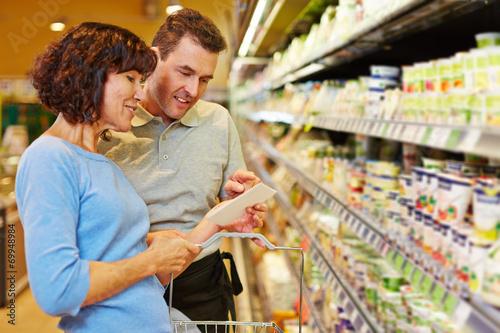 Verkäufer hilft Frau mit Einkaufsliste im Supermarkt - 69948984
