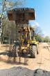 Wheel loader unloading fresh asphalt during road works