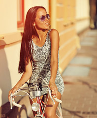 Fashionable woman with a bicycle on the street
