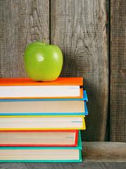Multi-coloured books and green apple .