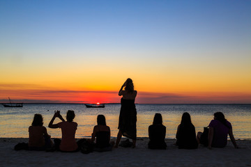 Women sitting on the beach watching the sunset