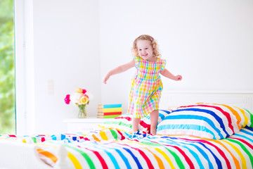 Cute little girl jumping on a bed