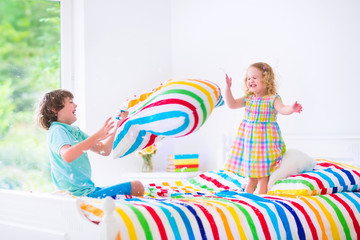 Adorable kids having pillow fight