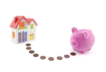 Saving for a house. Piggy bank with coins and house miniature.