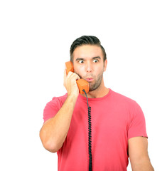 Portrait of young man in shock while talking on phone having unp