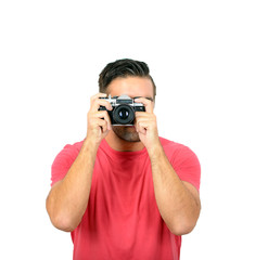 Young man using a retro camera against white background