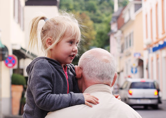 grandfather holding his 3 year old granddaughter