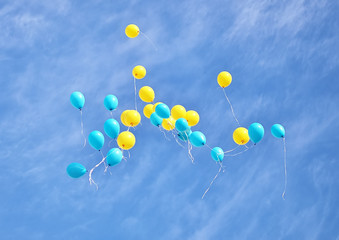 Yellow and blue balloons flying up in the sky