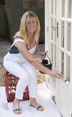 Woman painter decorator painting windows