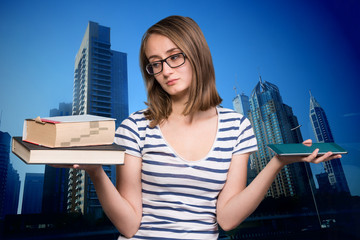 Young girl holding a book in one hand and a tablet-pc in the oth