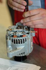 Hands of mechanic restores a generator