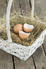 Close up of Egg and broken eggshell in white basket