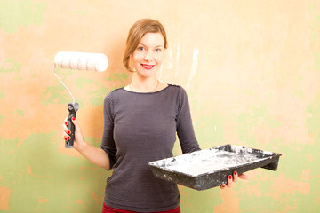 woman holding paint tray and roller.