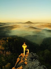 Man stay on the rocky peak and within morning watch to landscape