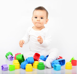 Beautiful baby girl with colorful toys - Studio shot