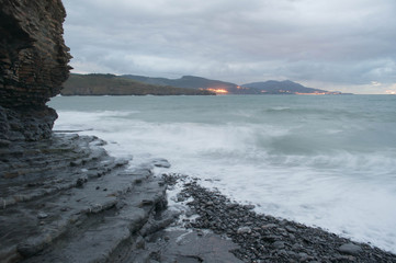 Rocky beach shore in a stormy sunset