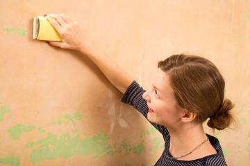 young woman sanding wall