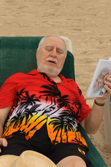 senior reader asleep at the beach while reading
