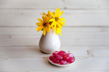 yellow flowers in a vintage vase with red candies