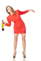 drunken young woman with bottle in hand, loses balance