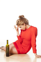 drunken young woman with headache sitting next to a bottle