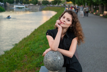 Young stylish girl in evening park near the river